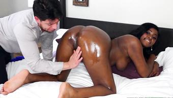 Веселая негритянка дрочит киску и дает мужику натереть маслом огромную жопу